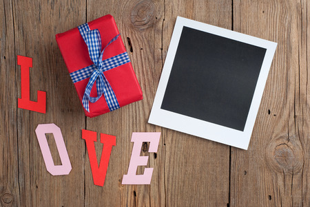 Instant photo with gift on old wooden background photo