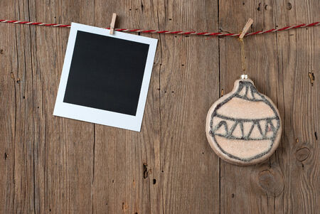 Christmas decoration with instant photo hanging on clothesline on old wooden background photo