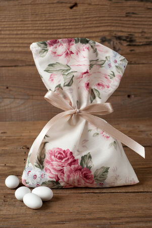 organza: Fabric pouch wedding favor on old wooden table