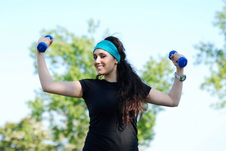 Beautiful young woman training with weights outdoor photo