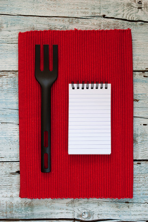 placemats: Notebook, placemats and fork on old wooden background