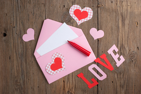 Handmade love letter with paper hearts and felt pen on old wooden background photo