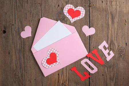 Handmade love letter with paper hearts on old wooden background photo