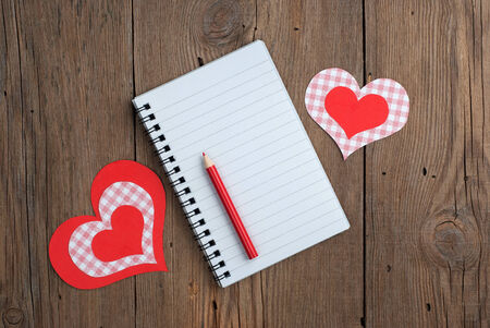 Notebook with paper hearts and red pencil on old wooden background photo