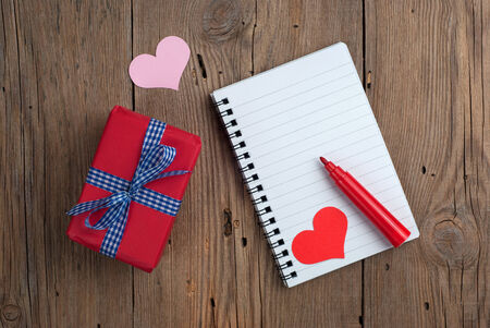 Notebook with gift box, felt pen and hearts on old wooden background photo