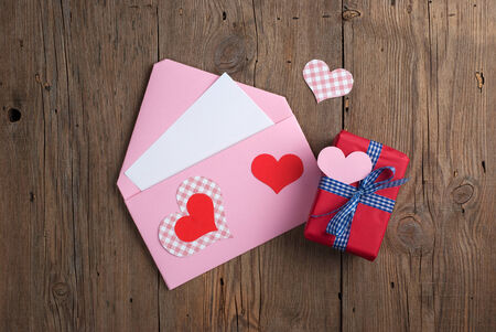 Handmade love letter with gift box and hearts on old wooden background photo