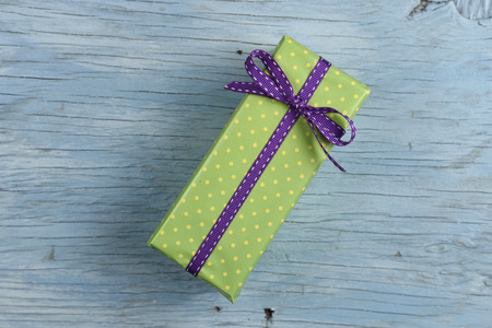 blue vintage background: Gift box with ribbon on old wooden table