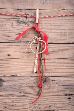 rope background: Wedding favor hanging on clothesline on old wooden background Stock Photo