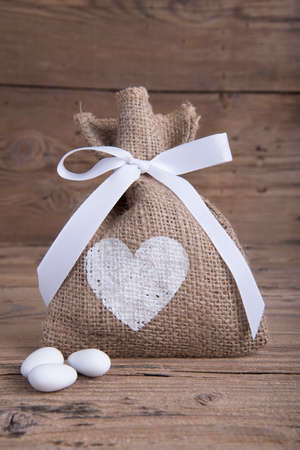 favor: Burlap wedding favor on old wooden table Stock Photo