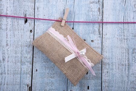 candy background: Wedding favor hanging on clothesline on old wooden background Stock Photo