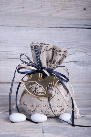sugarplum: Burlap wedding favor on old wooden table Stock Photo