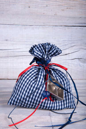 pouch: Fabric pouch tied with ribbon on old wooden table Stock Photo