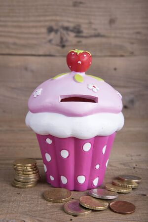 coin box: Ceramic cupcake coin box on old wooden table