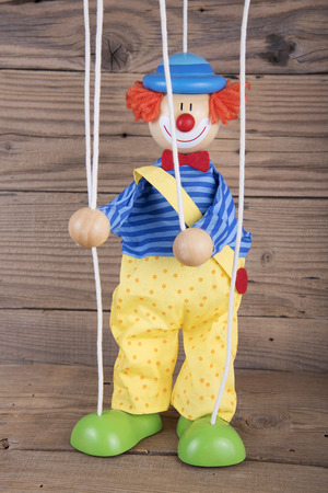 clown shoes: Clown puppet on old wooden background