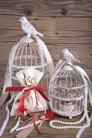 favor: Decorative bird cages with wedding favor on old wooden table