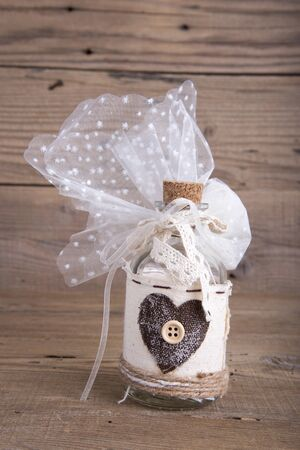 favor: Glass bottle wedding favor christening on old wooden table