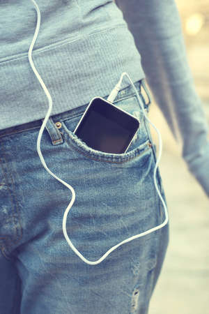 earpiece: Smartphone with headphones in front pocket of woman jeans