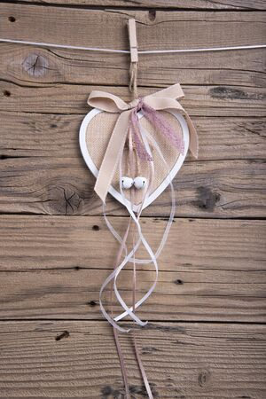 Wooden heart decoration with ribbons hanging on clothesline on old wooden background Stock Photo