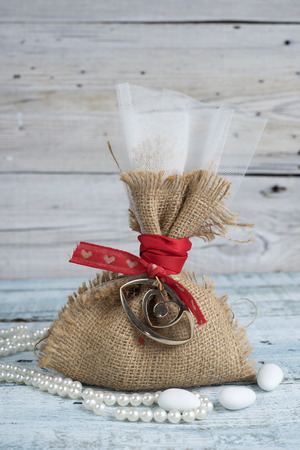 Burlap wedding favor on old wooden table Stock Photo