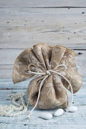 sugarplum: Burlap wedding favor on old wooden table Stock Photo