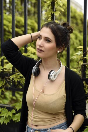Portrait of young beautiful woman with headphones around her neck