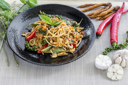 Spaghetti with clams, fried with chili paste in black bolw Stock Photo