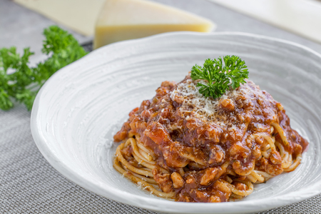 Spaghetti bolognese with cheese and pasley on a plate