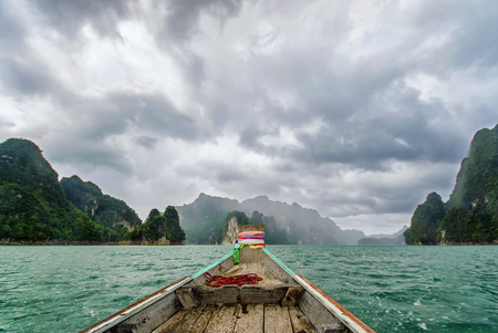 Khaosok or Ratchaprapa Dam in Southern of Thailand. The mountain and rain sky and longtail boat in the clear water. Stock Photo