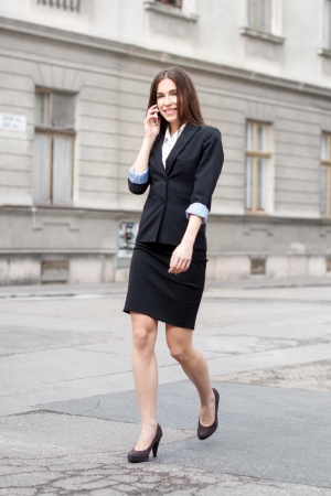 Successful brunette businesswoman calling on the street photo
