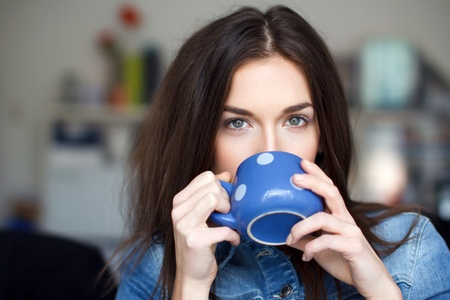 Young brunette woman with dotted blue mug drinking coffee photo