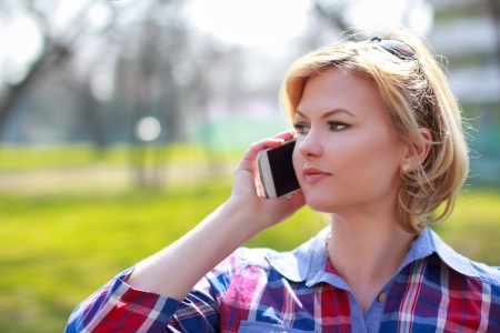 Attractive blonde woman calling with smartphone at park photo