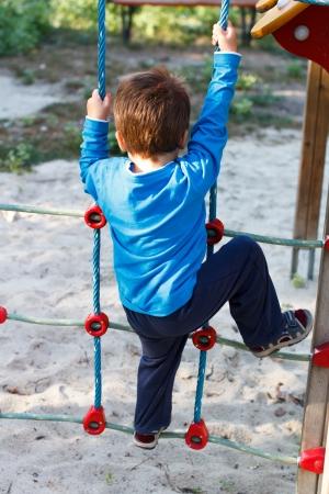 niño trepando: Niño pequeño que sube sin casco, peligroso, parque infantil