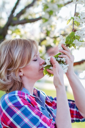Young woman smelling flower outdoor photo