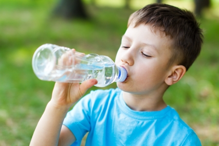 health drink: Little boy drink water, outdoor Stock Photo