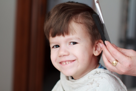 haircutting: Haircut for little boy, professional barber, teeth smile Stock Photo