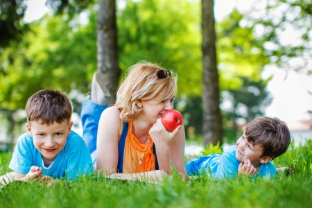 family health: Mother with sons and apple at outdoor, teeth smile, happy family