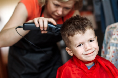 Haircut for little boy, professional barber, smile photo