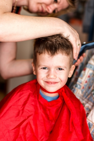 Mother cutting hair for son, smile photo