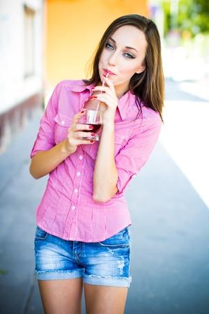 sexy young girls: Молодая женщина замачивания сосать сок с соломы, на открытом воздухе Фото со стока