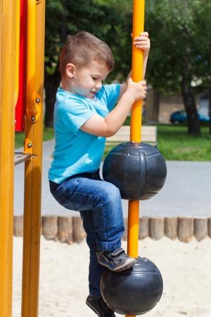ni�o escalando: Peque�a subida ni�o en el parque sin casco