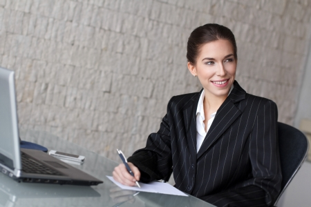 Young brunette businesswoman with laptop and smartphone, office photo