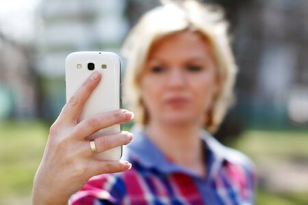Blonde woman online talk by smartphone, outdoor photo