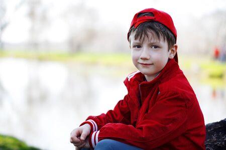 grandkid: Little child sitting on stone at river, nature