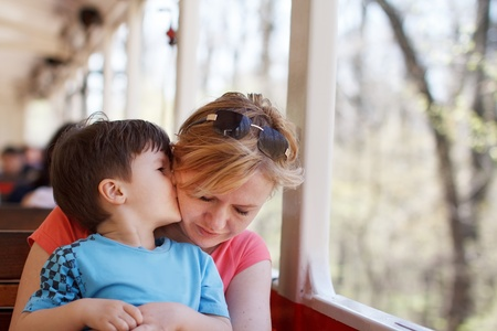 Boy hug mother on train, travel by rail photo