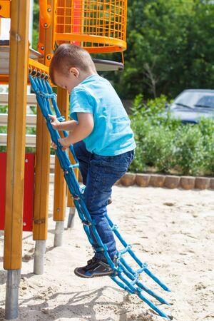 niño escalando: Chico lindo que sube en el patio