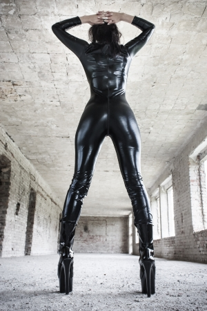 Sexy brunette fetish model posing in old industrial building, perfect body photo