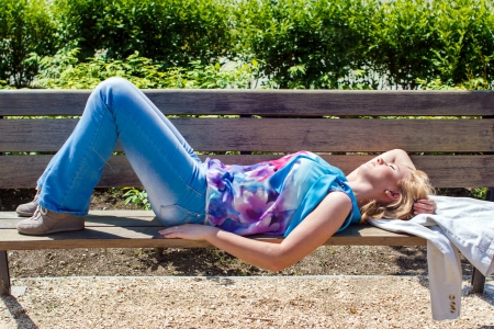 laying down: Young woman relaxing and sunbath at park on bench Stock Photo