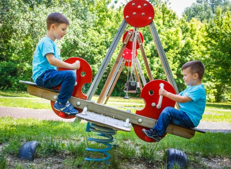 Little active boys on seesaw at playground, outdoors photo