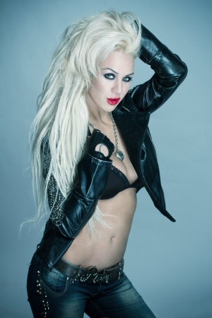 Sexy blonde woman rockstar posing in leather jacket photo