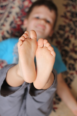 Smily little boy showing sole at home, childhood
